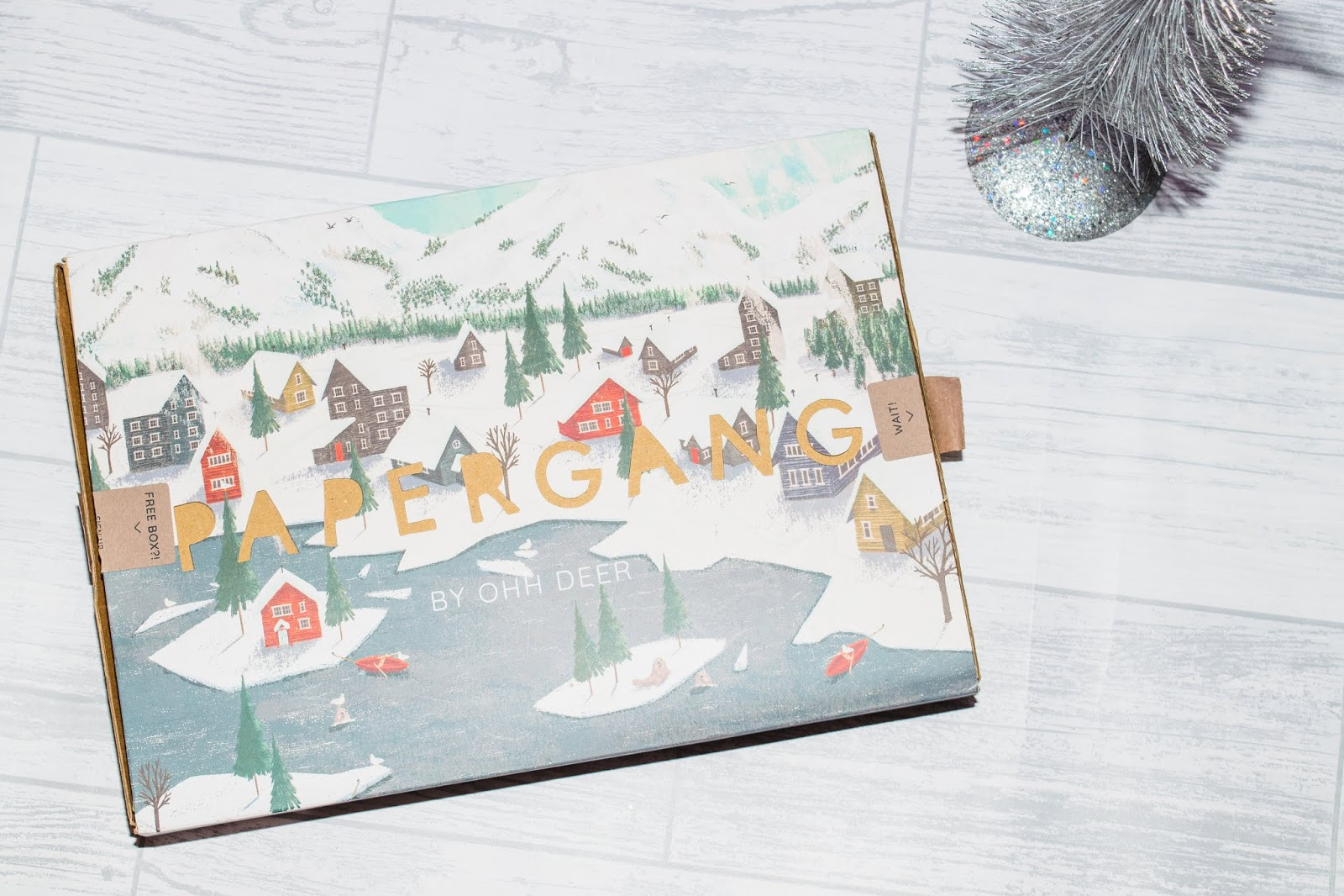 A box with the word 'papergang' cut out of the sleeve with a snowy forest design.