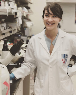 Camille Lake in a lab wearing a white lab coat