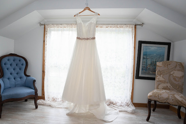 Detail shot of wedding dress hung by a bright window Magnolia Manor Wedding Photos by Stuart Wedding Photographer Heather Houghton Photography
