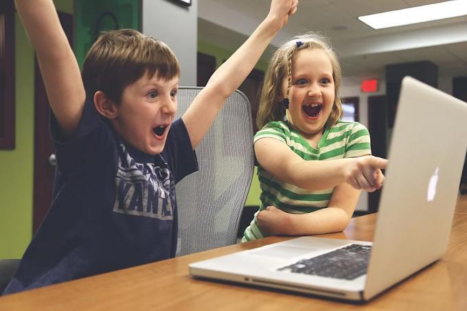 Um menino e uma menina comemorando algo que estão vendo na tela de um laptop