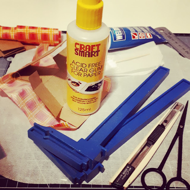 1/12 scale cardboard chair kit with fabric attached and a glue bottle weighing it down while drying.