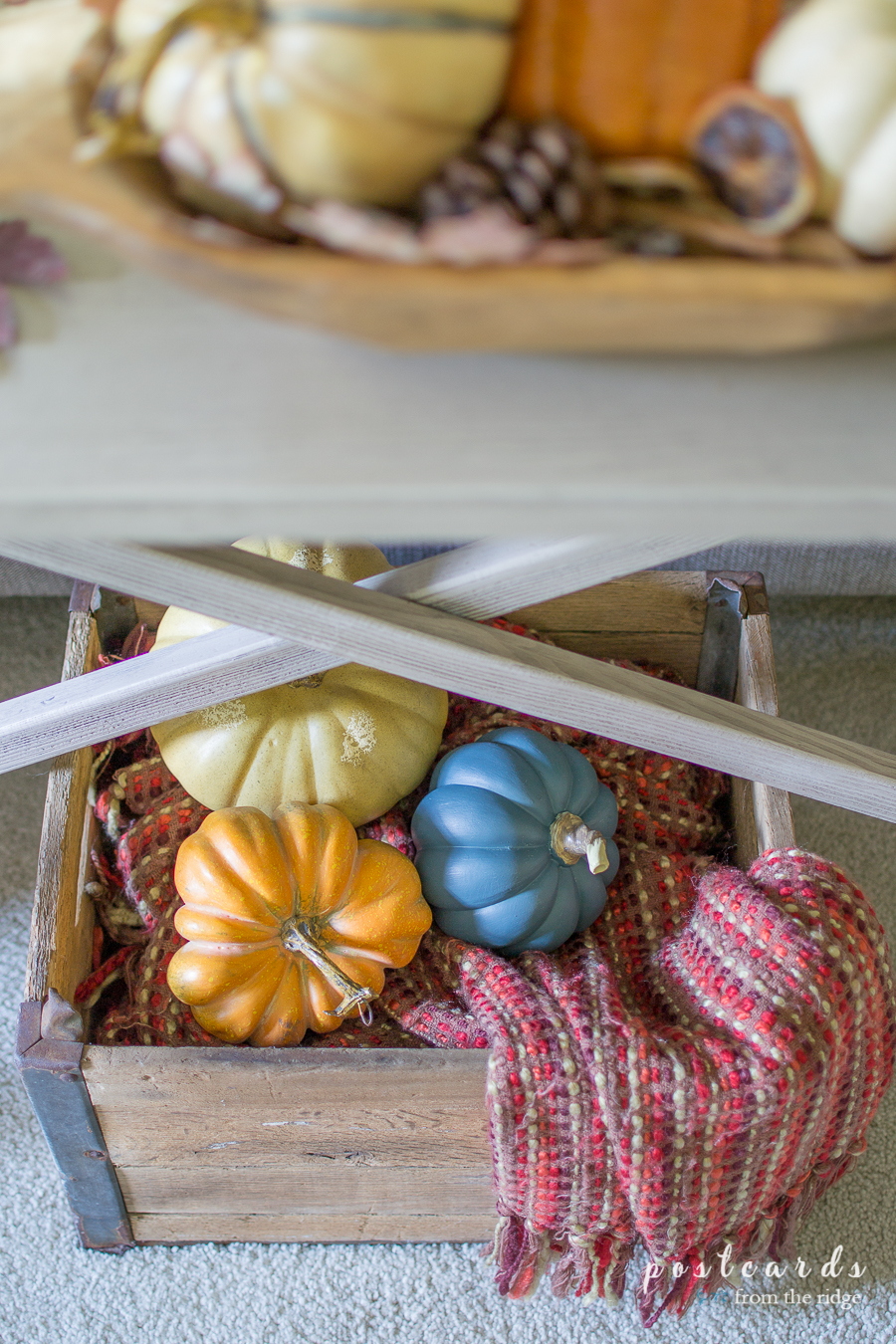 faux pumpkins and throw blanket in wood crate