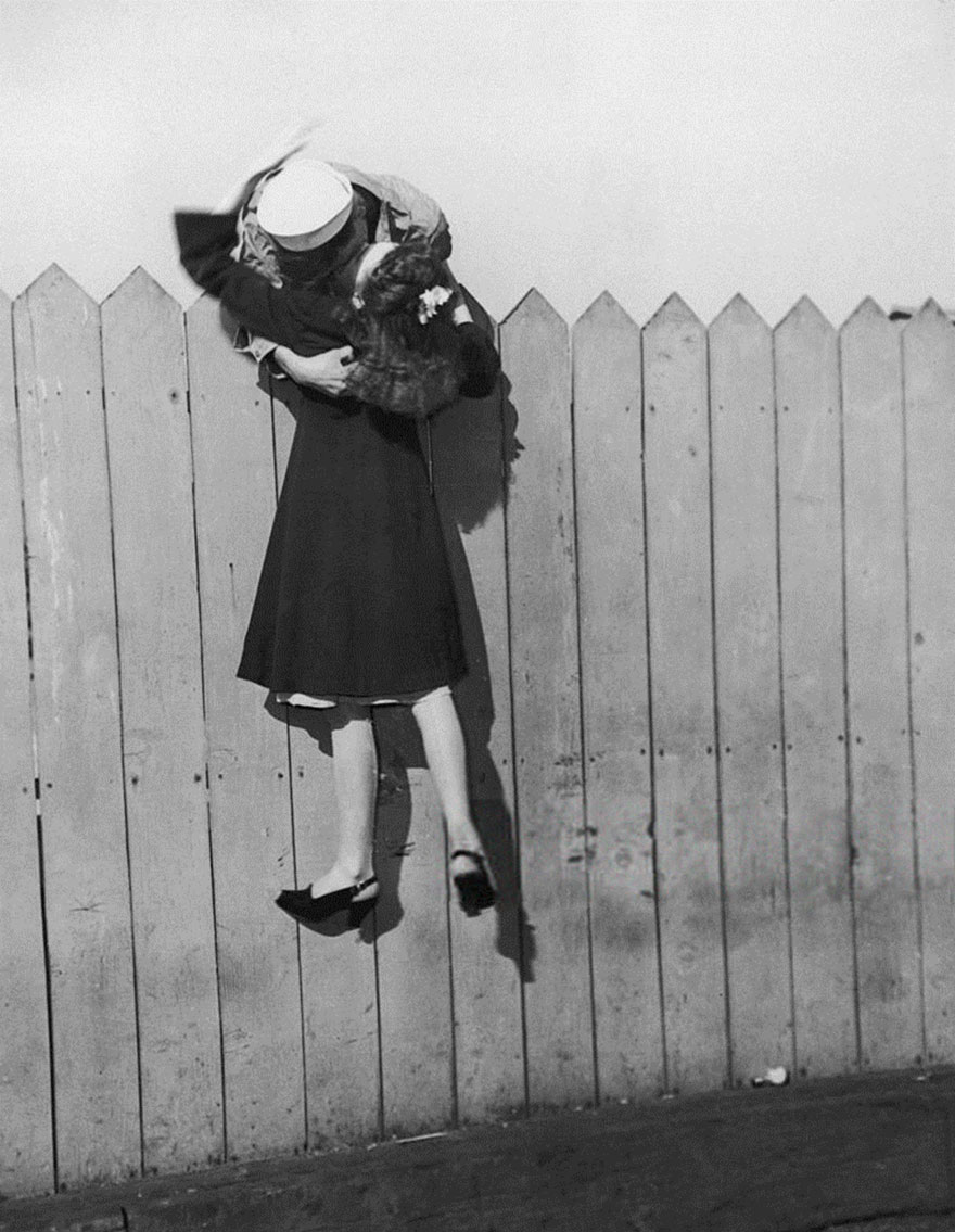 60 + 1 Heart-Warming Historical Pictures That Illustrate Love During War - A Sailor Leans Over A Picket Fence And Lifts His Girlfriend Up For A Kiss, 1945