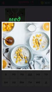 на столе стоят тарелки с супом и в чаше находится мед