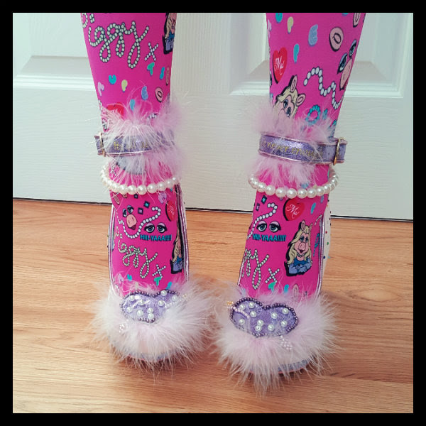 close up of feet wearing pink Miss Piggy tights and Irregular Choice satin shoes with fluffy heart detail