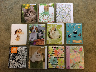 Assorted spiral notebooks with covers showing kittens, flowers, or abstract designs