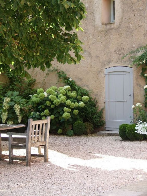 Peaceful French farmhouse exterior with hydrangea and pea gravel courtyard on Hello Lovely Studio