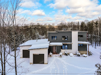 a drone view of a house in winter season with appearance of a regular photo but the exterior cladding is applied digitally.