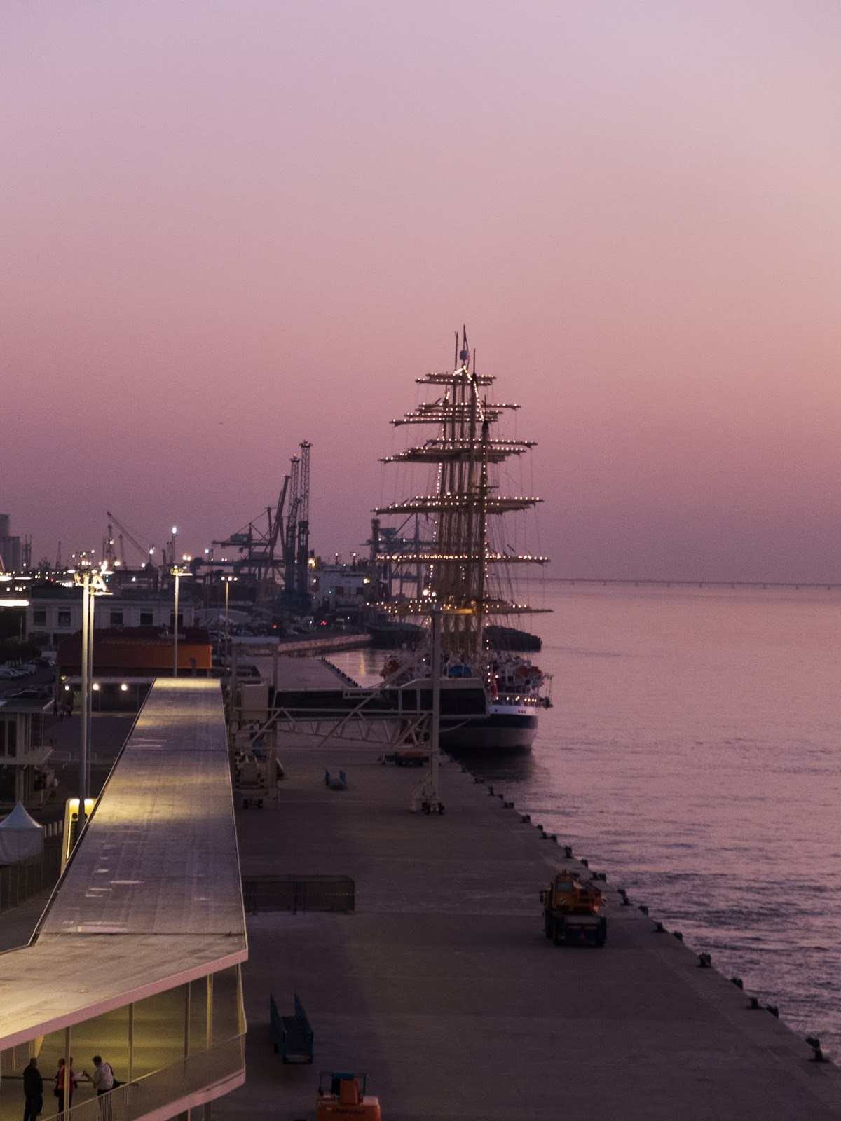 A ship docked at the port of Lisbon captured at sunrise.