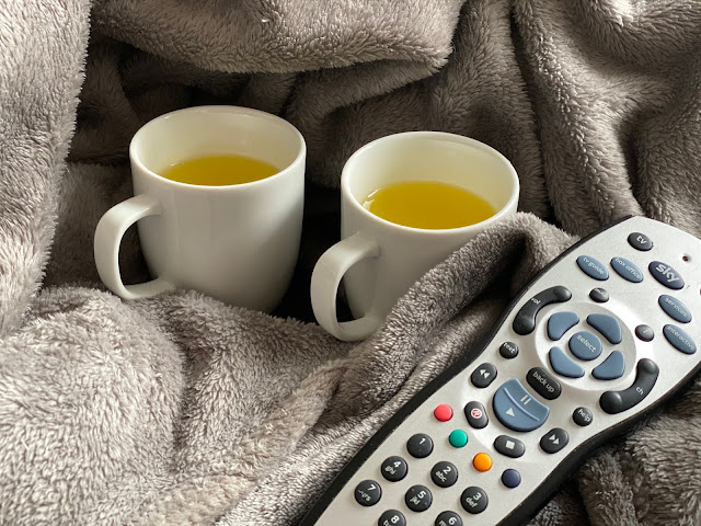 a fluffy warm blanket, 2 small white mugs with warm orange squash in and a sky remote
