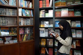 Membaca buku di perpustakaan