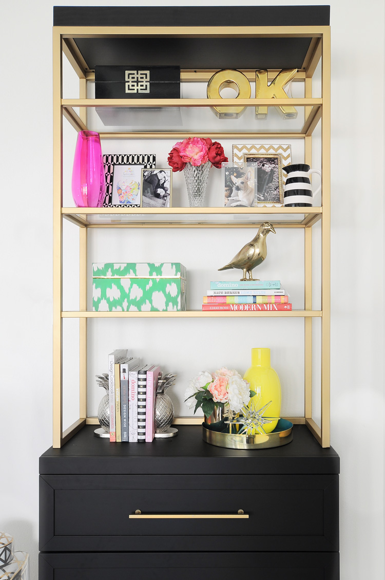 A black and gold etagere bookcase styled to perfection with bold, colorful and glam decor accents.