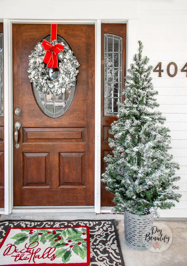 front door with flocked wreath and tree