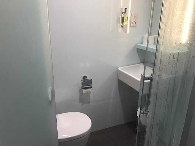 view into the easyhotel Manchester bathroom from the door way. The toilet, shower door and sink are visible
