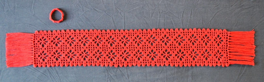 The second Diamond Strike Scarf (B) in full view, displayed horizontally with the separate band fastening above it.  This scarf has 15cm straight fringe on each short end. The body pattern consists of 14 rows of filet crochet spiderweb motifs (2 per row) and the long sides have ridged edges created by a scallop border pattern. These ridges hold the band in place when wearing the scarf so that it doesn't slip off.