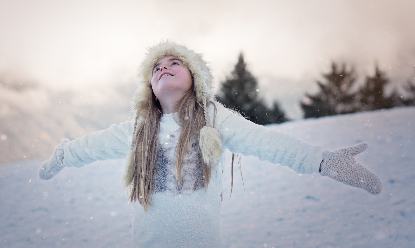 雪の中で腕を広げた女性