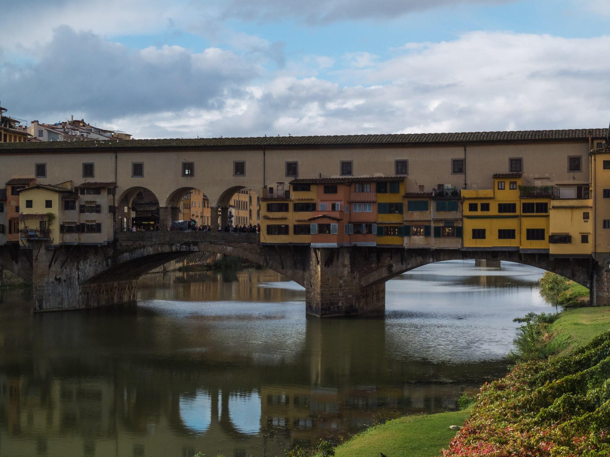Ponte Vecchio reflecting in the river Arno in Florence.