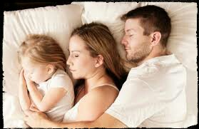 A father , mother and child sleeping