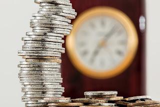Varias moedas empilhadas e um relógio desfocado ao fundo
