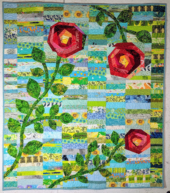 Chinese Coin background with three large red roses of improvisational log cabin piecing. The stems and leaves are green batik applique.