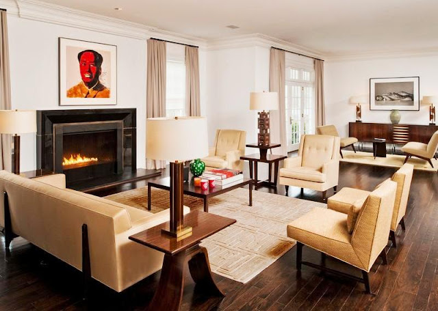 Living room in a mansion with wood floor, fireplace with a Warhol style portrait on the mantel, french doors with neutral floor length curtains and matching arm chairs and sofa.