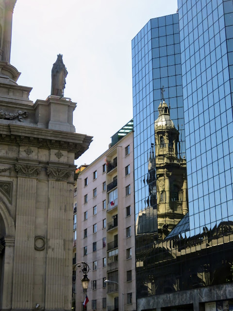 Colonial building reflected in a modern glass building on Plaza de Armas in Santiago Chile