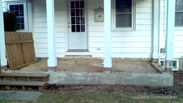 Covered porch in disarray with dirt floor