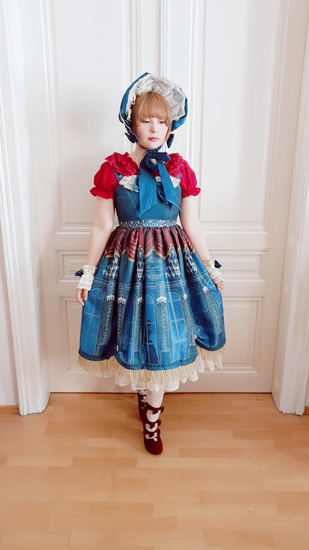 auris wearing the navy elisabeth dress from classical puppets with a bonnet and a red blouse