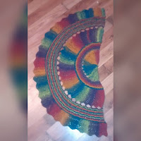 A multicoloured shawl with several sections, each with its own lace pattern.