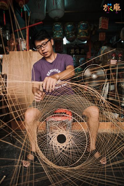 唐嘉興老師坐在店面專心地編織竹燈籠