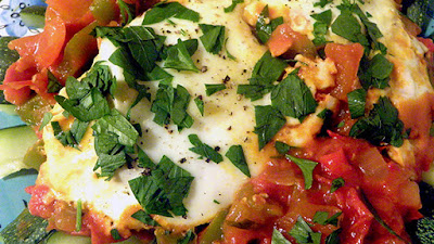 closeup of tomato sauce, eggs, parsley, and black pepper