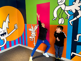 Two boys standing in front of a brightly coloured wall