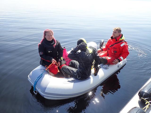 Kolme biologia pienessä kumiveneessä. Kaksi valmistautuu sukellukseen.