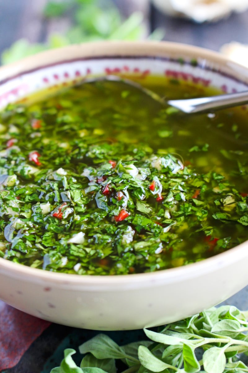 Side view closeup of Chimichurri Sauce in a tan bowl.