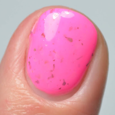 neon pink nail polish with color shifting flakies close up
