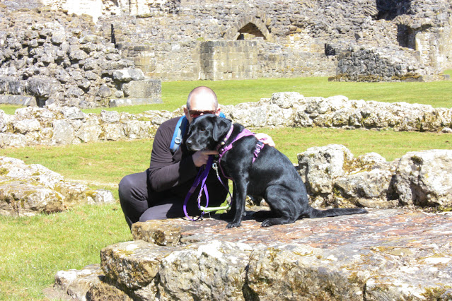 Neil and Liggy (black lab) are sitting together on a large stone, part of a ruin. Neil's face is partly hidden behind Liggy's as he is gently nuzzling her face.