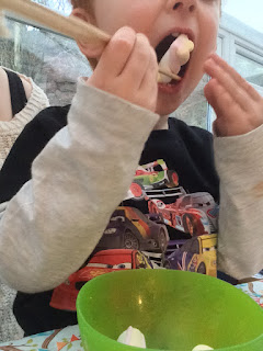 Toddler using chopsticks to eat marshmallows