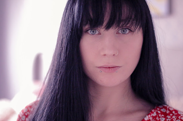 Close up photo of Jordanne (@ofaglasgowgirl) with long black hair looking into camera in a red flower dress