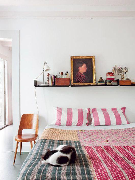 Silla de madera como mesita de noche en un dormitorio colorido