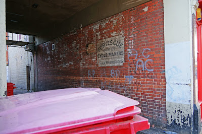 A photograph of the ghost sign and surrounding alleyway: the red brick wall, covered with graffiti tags, joins onto a flat concrete roof. To the left of the picture, a daylit yard is visible; to the right, a colourful shop front. In the foreground is the top of a large red commercial bin, bleached pink by the sun.