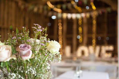 A floral centre piece of purple and yellow roses on a white tablecloth in a rustic old barn.