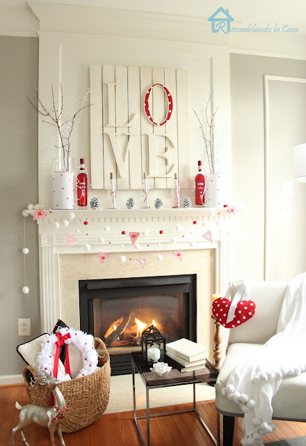 Valentine mantel with branches, love art and pom pom garland