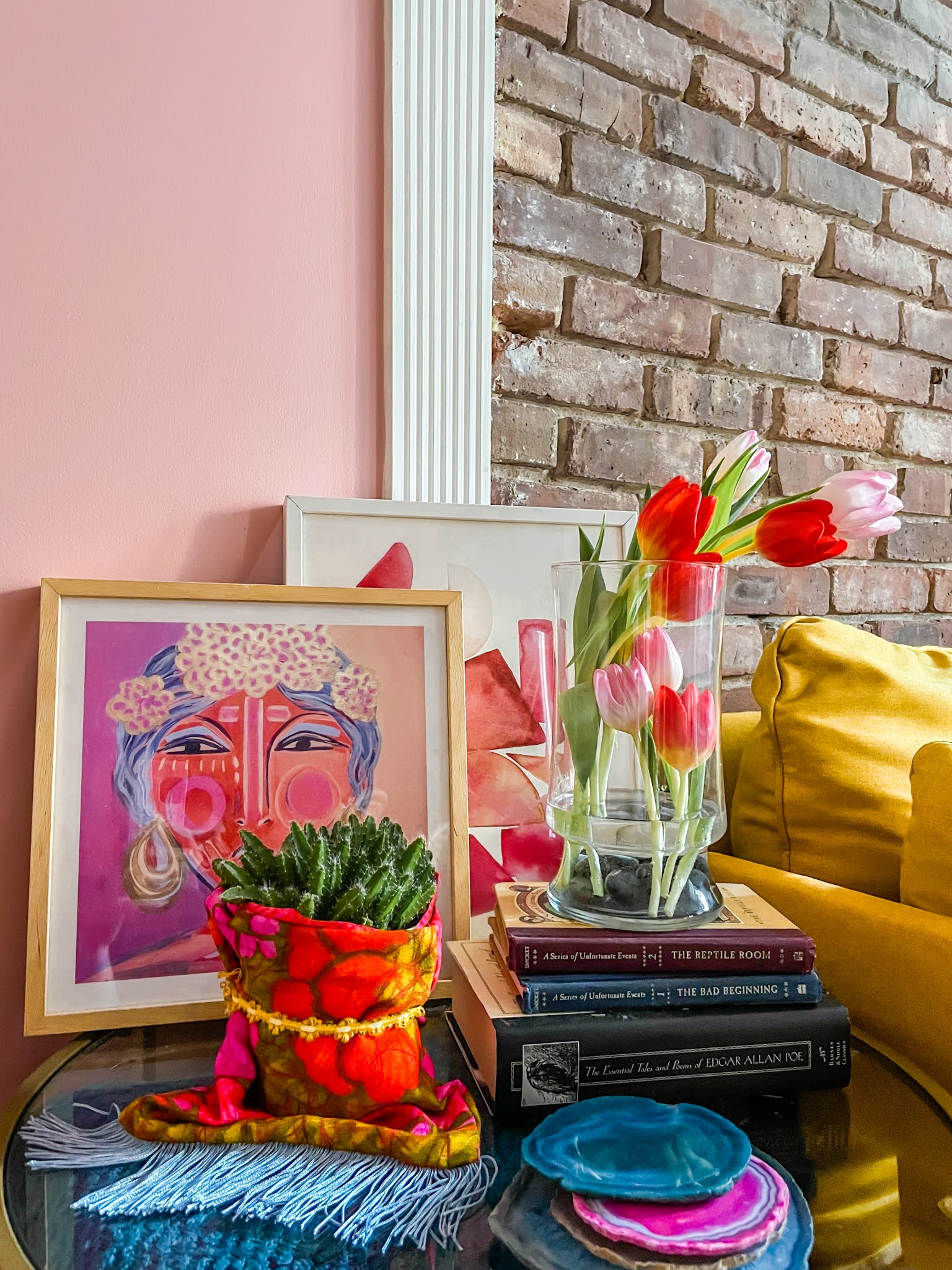 Pink decor // how to add color to your home // pink art work // tulip flower arrangement // side table styling // colorful living room // dragonfruit plant // layered frames // flower arrangements