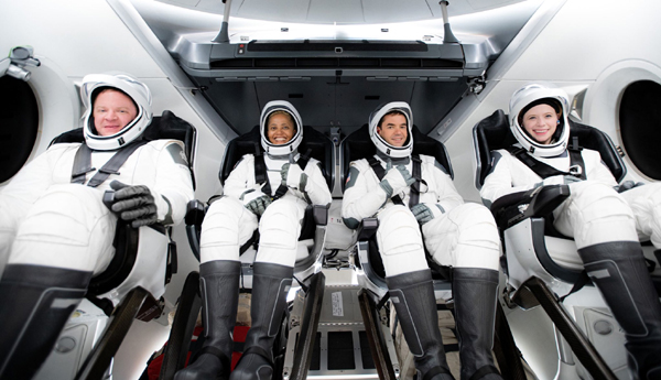 The Inspiration4 astronauts pose for a group photo inside the Crew Dragon flight simulator at SpaceX Headquarters in Hawthorne, California.