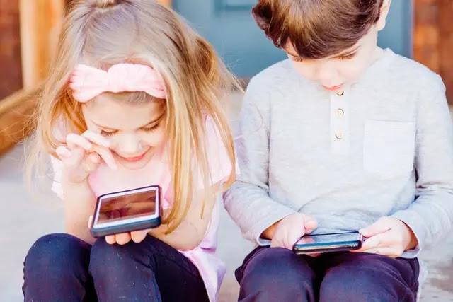 Un niño y una niña sentados uno junto al otro viendo la pantalla de su celular