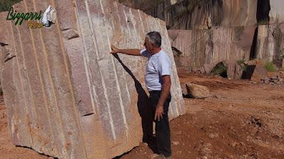 Bizzarri, da Bizzarri Pedras, observando um bloco de pedra de granito vermelho e imaginando cortar a pedra para mesa de pedra, banco de pedra e pedra para jardim.