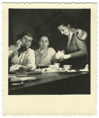Altes Schwarz-Weiß-Bild: Telefon, Kuchen und Tee, gute Laune im Büro