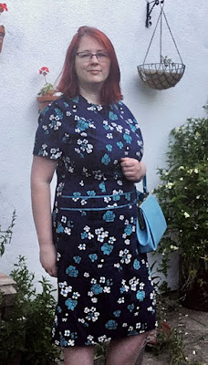 A redheaded woman in a navy dress with turquoise and white flowers.