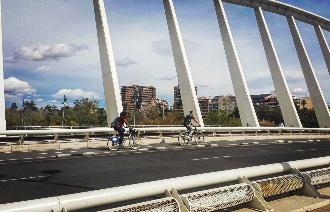 Cyclists crossing La Exposición bridge by Santiago Calatrava in Valencia, Spain