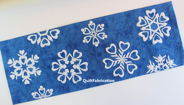 white heart themed snowflakes on a blue background for a table runner by QuiltFabrication